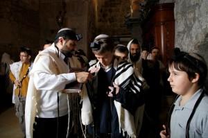 עורך תפילה מדריך את חתן בר מצווה
